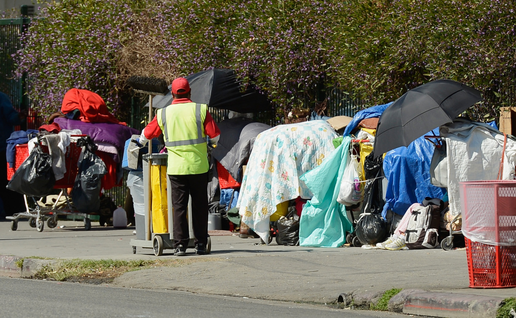 A member of a clean-up crew looks at belongings of a homeless person on a public sidewalk February 28, 2013 in downtown skid row area of Los Angeles, California.