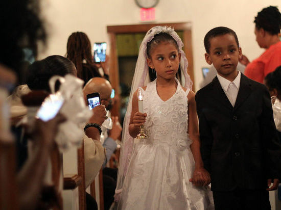 A young couple walks down the aisle in a recent Tom Thumb wedding on Staten Island.