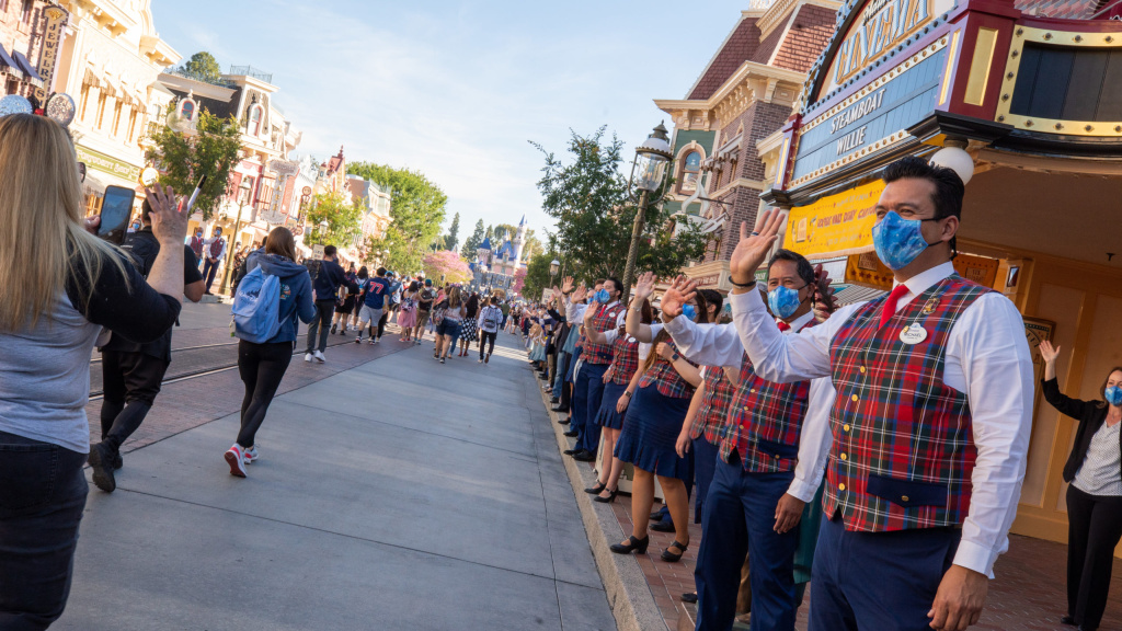 In this handout photo provided by Disneyland Resort,  Guests as are waved to by workers as they take in the sights and sounds of Main Street U.S.A. at the Disneyland Resort on April 30, 2021 in Anaheim, California.