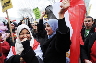 A woman, right, waves a flag at a rally formed by a coalition of Egyptian-American groups February 12, 2011 in New York supporting the protesters in Egypt one day after a popular revolt drove veteran strongman Hosni Mubarak from power.