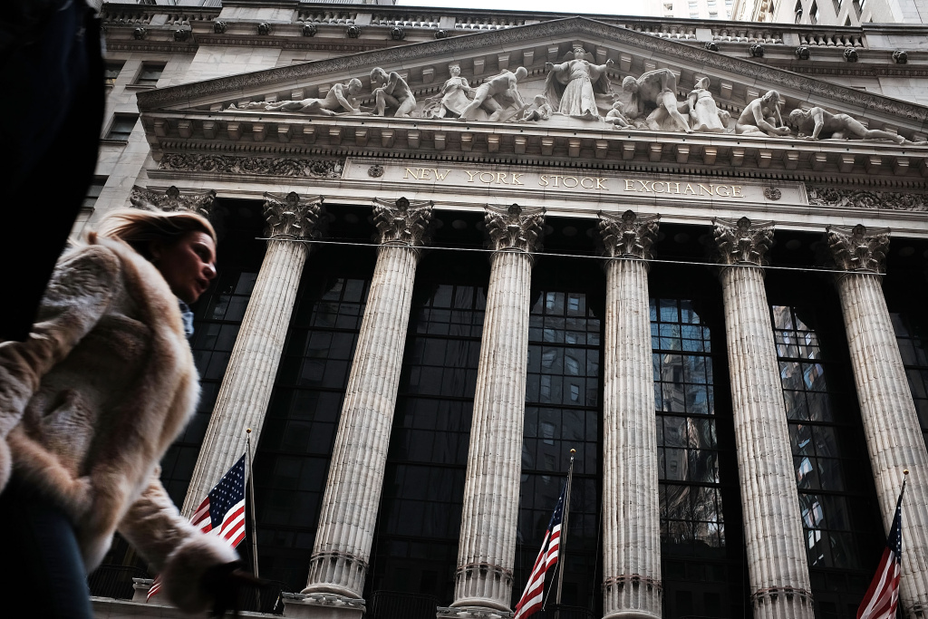 People walk by the New York Stock Exchange (NYSE) on January 15, 2016 in New York City. Stocks have fallen significantly in morning trading with the Dow Jones industrial average down over 400 points as concerns about oil prices and the Chinese economy persist.