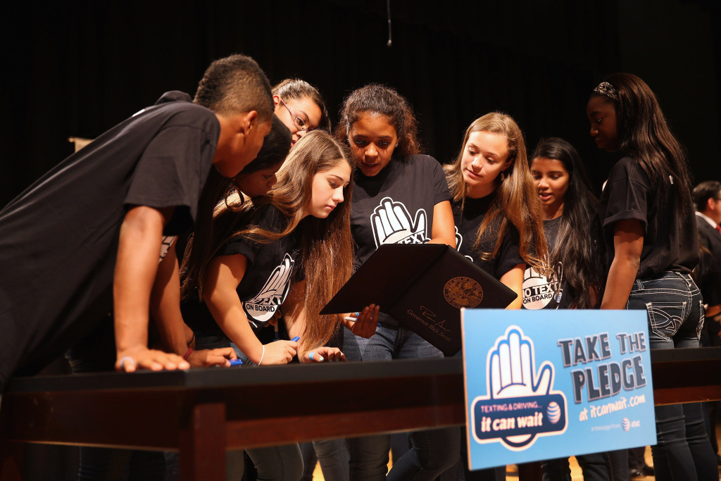 Brittany Ortiz (C) and Jaimie Waxman (2nd L) and other high school students look at the signature of Florida Governor Rick Scott on Florida Senate Bill 52, after he signed the legislation to ban texting while driving.