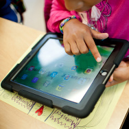 L.A. Unified has already purchased 75,000 iPads, half with Pearson software. Here, second graders at Baldwin Hills Elementary swipe through their iPads for the first time and call out the apps they see.