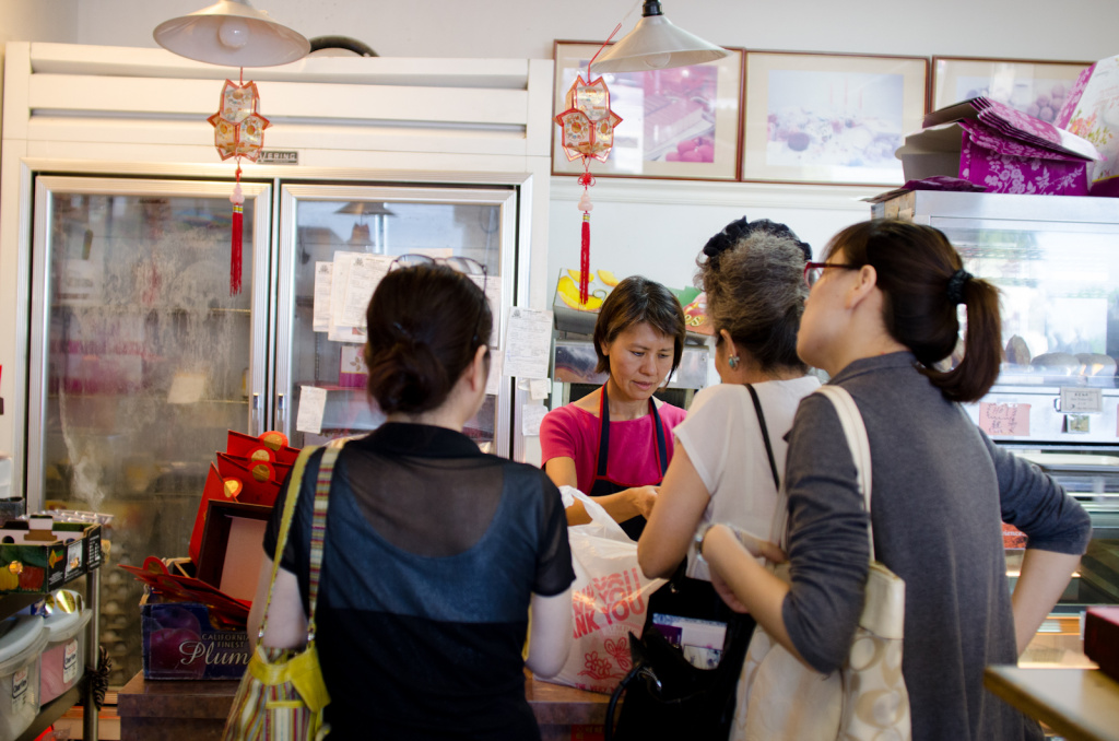 Nancy Yang, owner of Olympic Bakery, helps customers with their orders of Mooncake and other pastries in Temple City, Calif., Monday September 24, 2012. The small pastries are made for the Chinese Moon Festival which takes place during the eight lunar month each year.