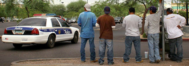 A police cruiser passes by a group of day laborers on a curbside in Phoenix on Monday.