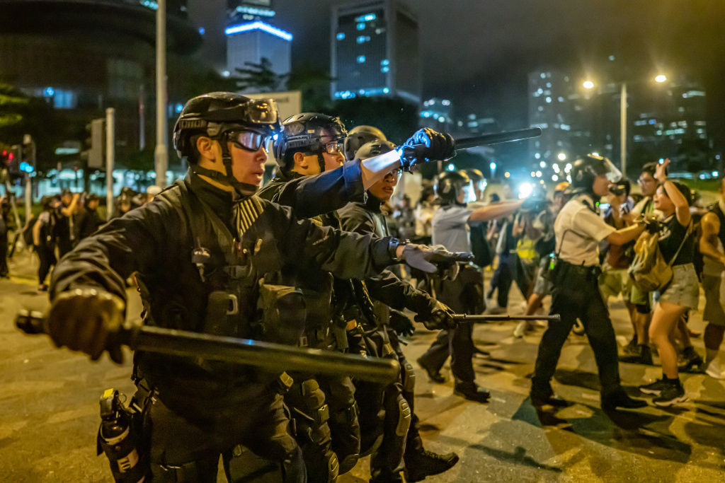 Police officers charge toward protesters after a rally against the extradition law proposal at the Central Government Complex on June 10, 2019 in Hong Kong China