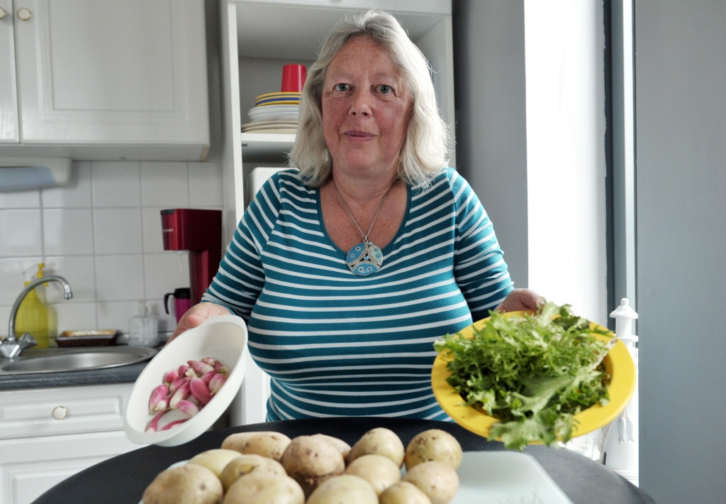 Andree Nieuwjaer shows radishes, lettuce and potatoes in her kitchen, on November 27, 2015 in Roubaix, northern France. She and her family are part of the 101 households that took on the