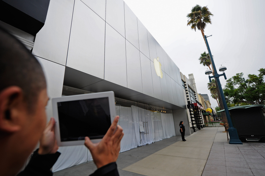 A man uses his iPad to take a picture of an Apple store closed to the public to allow employees to watch a webcast of a celebration of Steve Jobs' life from the company's headquarters in Cupertino, Calif., on October 19, 2011, in Santa Monica, Calif. Jobs succumbed to pancreatic cancer.