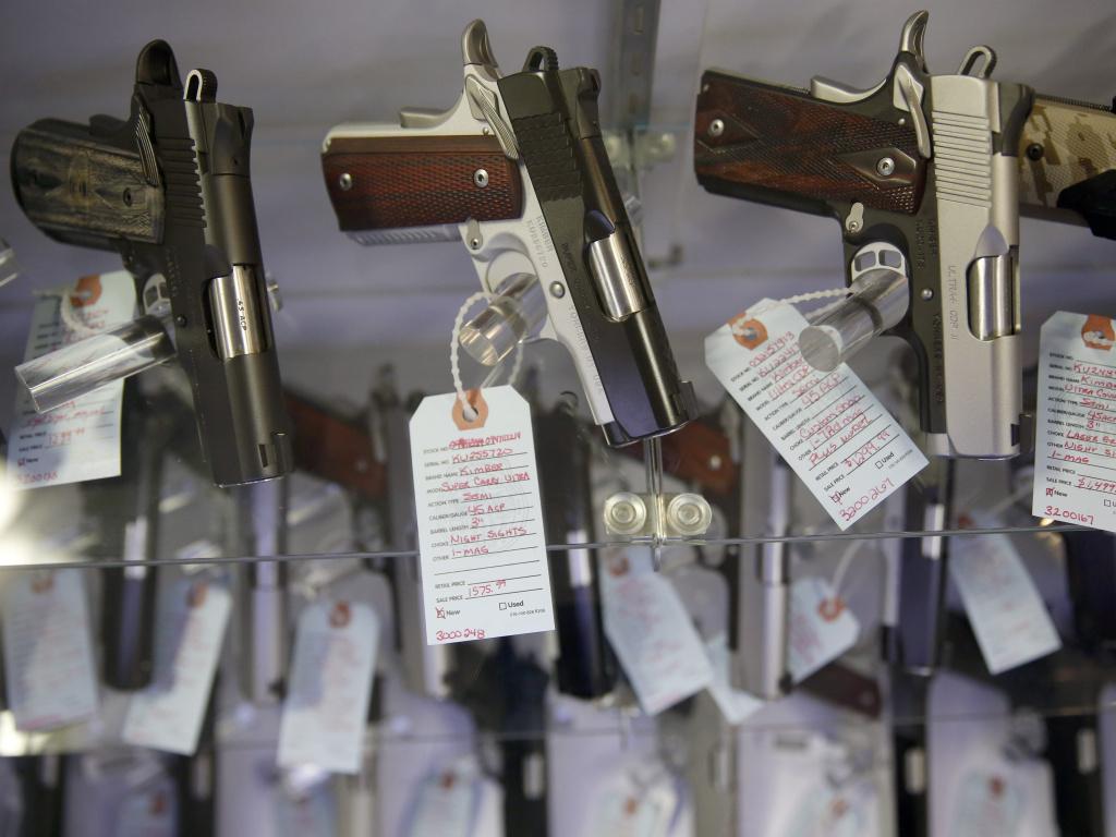 Handguns sit in a glass display case in Bridgeton, Mo.