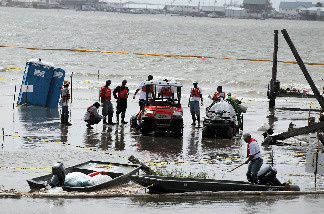 Oil cleanup workers salvage their equipment after water, pushed by high seas, inundated their oil boom containment staging area on July 7, 2010 in Grand Isle, Louisiana.