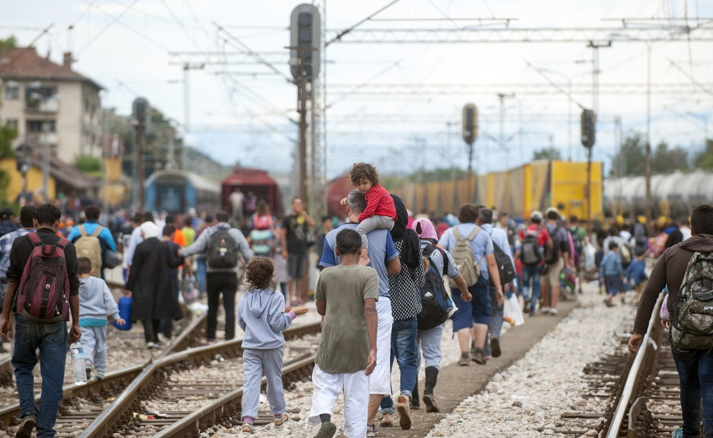 Migrants walk on train tracks towards the town of Gevgelija after broking a cordon of Macedonian special police forces on August 22, 2015. Hundreds of refugees broke through barbed wire fencing bordering Macedonia despite a heavy police presence. Macedonia said it had declared a