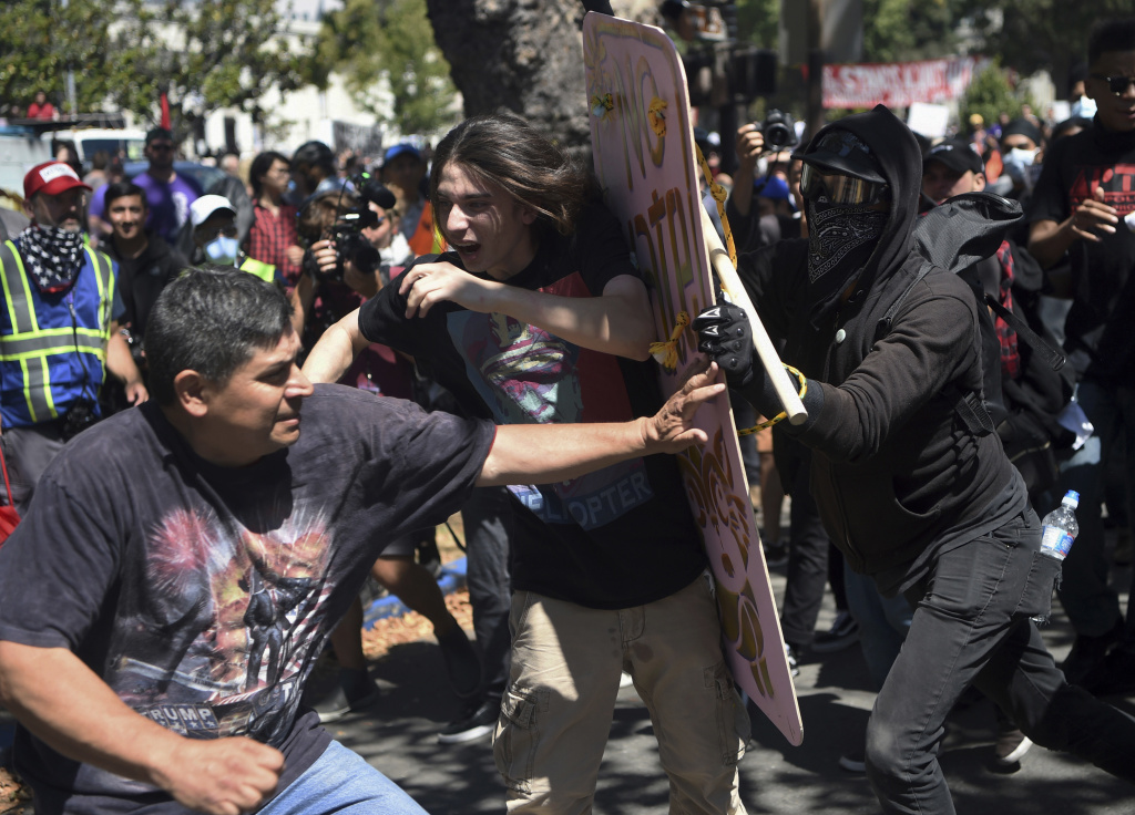 FILE - In this Aug. 27, 2017 file photo, demonstrators clash during a free speech rally in Berkeley, Calif. Police in Berkeley, California say they need an additional weapon to combat violent protests that have repeatedly hit the city. The city council will decide Tuesday, Sept. 12, 2017, whether to let officers use pepper spray to control crowds that turn violent. (AP Photo/Josh Edelson, File)