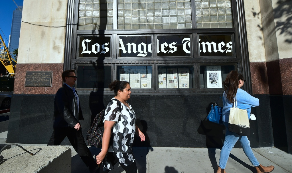 Pedestrians walk past The Los Angeles Times office building in Los Angeles, California on February 7, 2018, where billionaire Patrick Soon-Shiong reached a deal to buy the newspaper from Tronc, its Media Company owners.