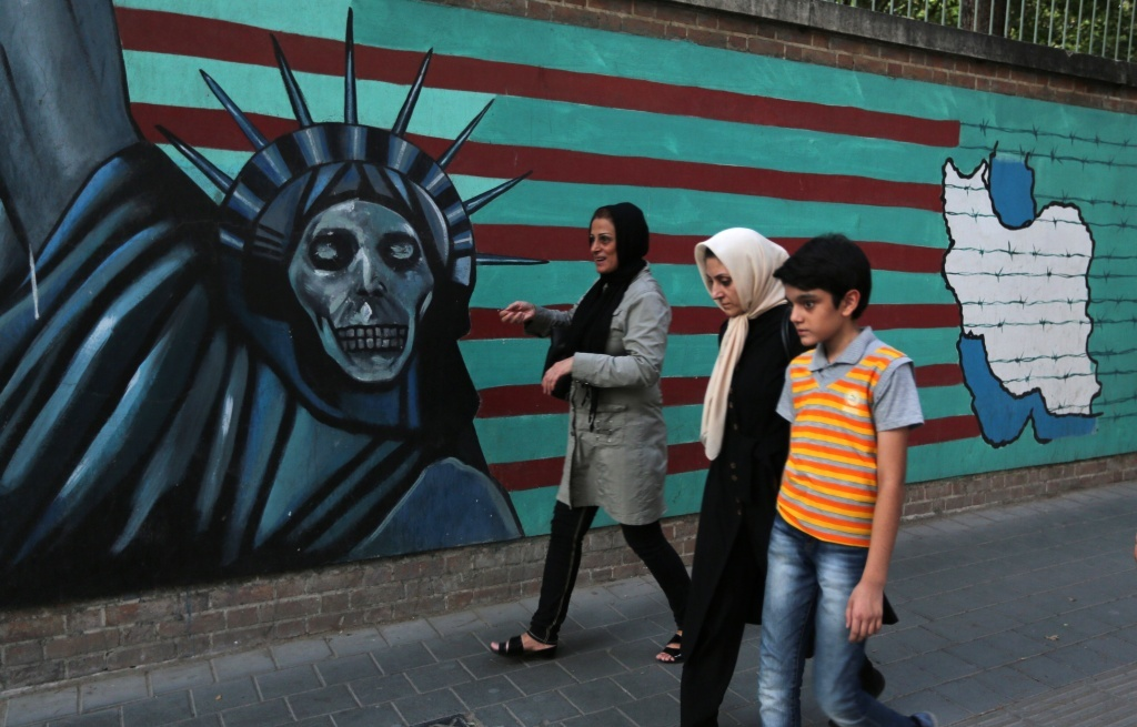 An Iranian family walks past anti-U.S. graffiti on the wall of the former U.S. embassy in Tehran on Tuesday. President Hassan Rouhani told Iranians that