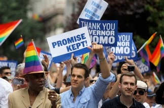 Marchers hold signs thanking Governor Andrew Cuomo for keeping his campaign promise and legalizing Same-Sex Marriage during the 2011 NYC LGBT Pride March on the streets of Manhattan on June 26, 2011 in New York City.
