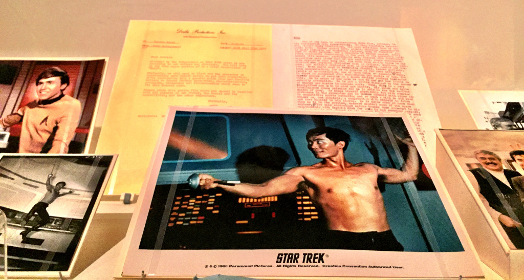 """Star Trek memorabilia at the Japanese American National Museum's exhibit """"New Frontiers: The Many Worlds of George Takei."""" At the top is a letter to George from Gene Roddenberry with Sulu character notes. In the center, a still of George in The Naked Time."""
