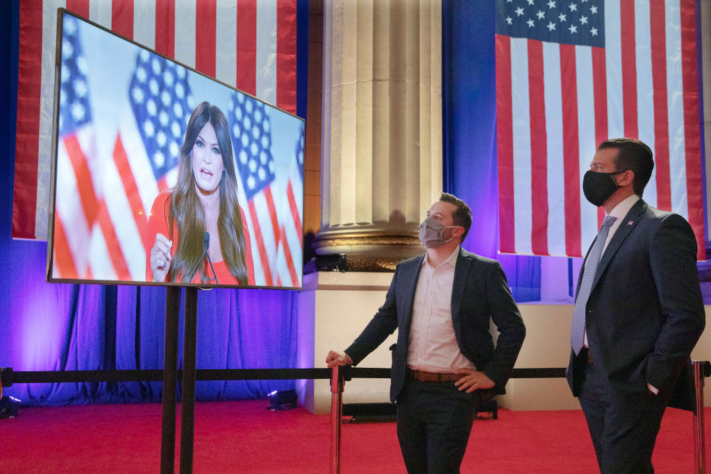 Wearing a face mask to reduce the risk of transmission of the novel coronavirus, Donald Trump Jr. (R) watches his girlfriend Kimberly Guilfoyle as she pre-records her address to the Republican National Convention at the Mellon Auditorium on August 24, 2020 in Washington, DC.