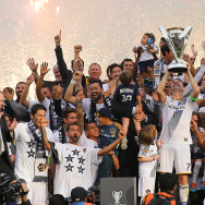 Captain Robbie Keane #7 of the Los Angeles Galaxy hoists up the Philip F. Anschutz Trophy on the podium as his Galaxy teammates cheer on after the Galaxy defeated the New England Revolution 2-1 in the 2014 MLS Cup at StubHub Center