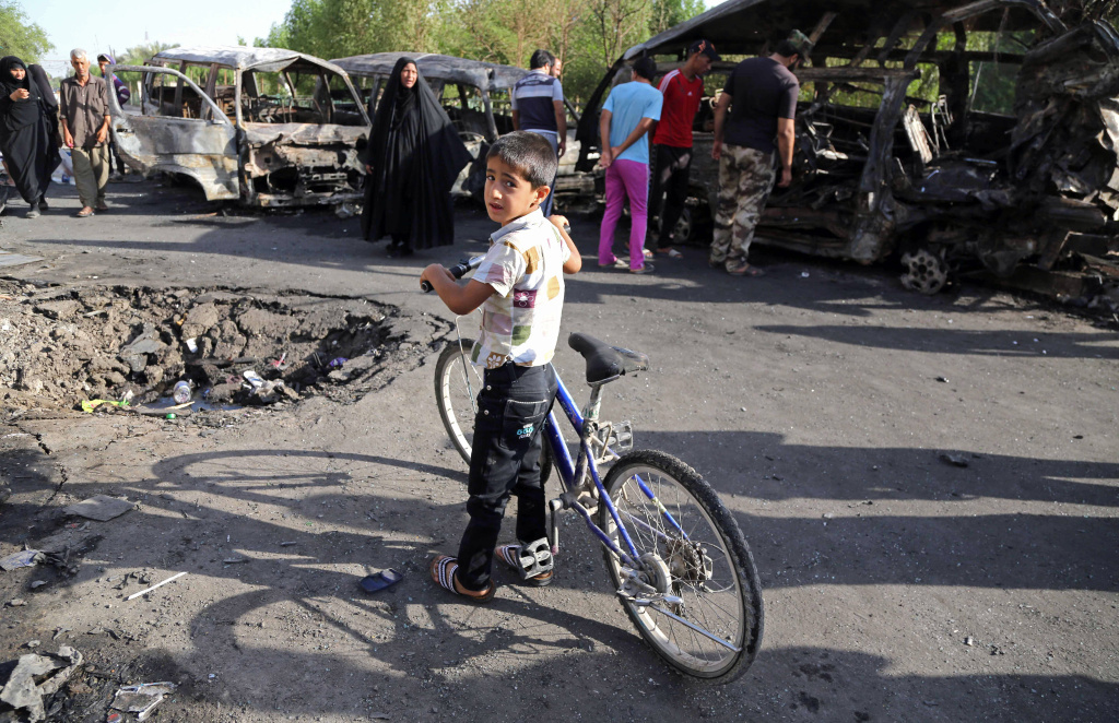 An Iraqi boy and other civilians look at the aftermath of a car bomb in Baghdad's Sadr City Wednesday. The violence in the Shiite district comes as Sunni militants advance in northern Iraq.