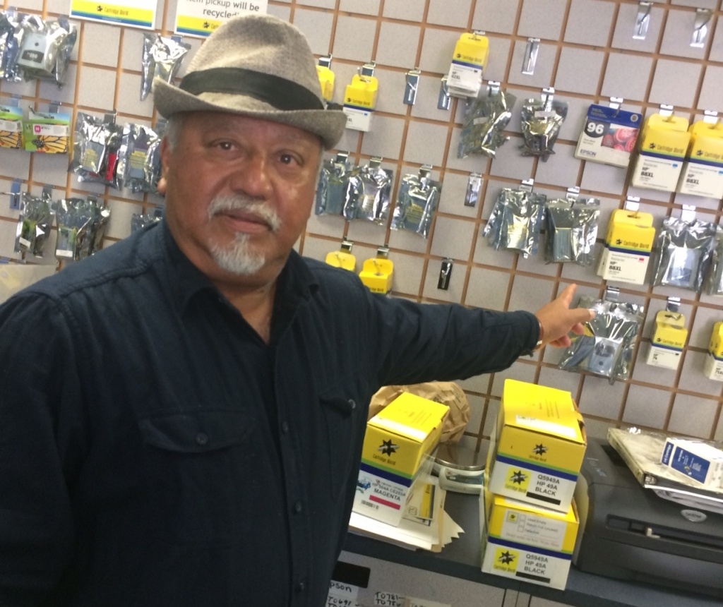 Omar Huda, 65, points out printer supplies in his Pasadena store. He says his family's shrimp business in Bangladesh was destroyed after a 2007 cyclone, forcing his cousins to the capital, Dhaka.