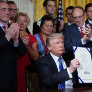 President Trump holds up the signed Department of Veterans Affairs Accountability and Whistleblower Protection Act of 2017 on Friday.