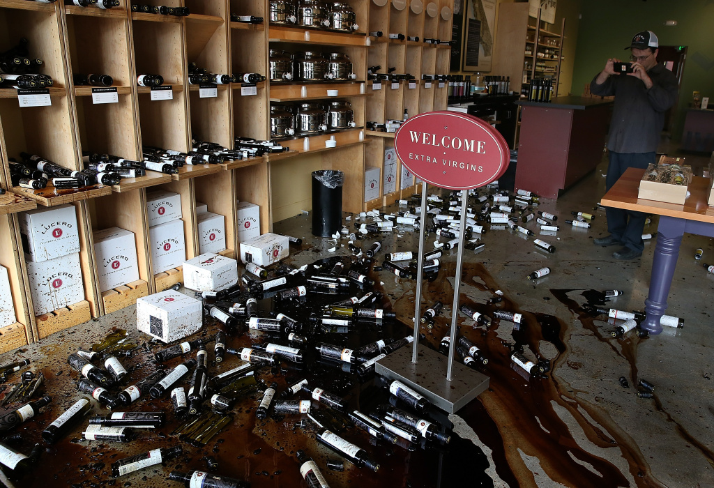 NAPA, CA - AUGUST 24:  A worker takes a picture of bottles of olive oil and vinegar that were thrown from the shelves of an olive oil store following a reported 6.0 earthquake on August 24, 2014 in Napa, California. A 6.0 earthquake rocked the San Francisco Bay Area shortly after 3:00 am on Sunday morning causing damage to buildings and sending at least 70 people to a hospital with non-life threatening injuries.  (Photo by Justin Sullivan/Getty Images)