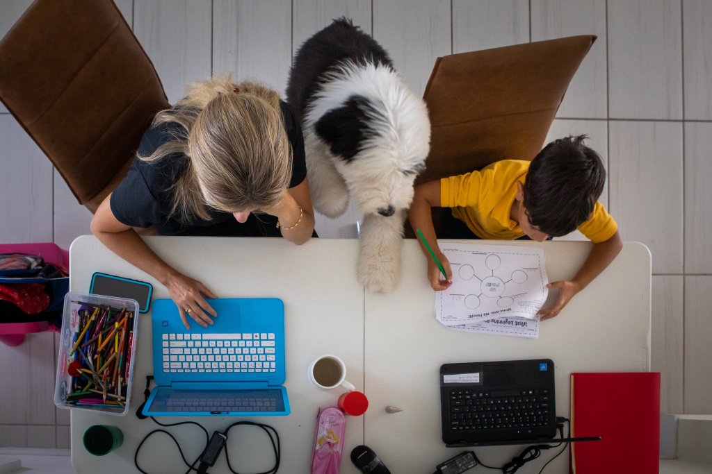 A mother works from home while her son attends school remotely in an arranged photograph taken in Miami in September.
