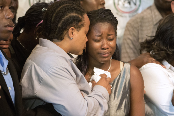 In this Sept. 29, 2016 file photo, the daughter of Alfred Olango gets tearful while listening to her grandmother, Pamela Benge speak of her son, Alfred Olango, at a press conference in San Diego, Calif., to address the killing of Olango, a Ugandan refugee shot by an El Cajon police officer. Attorney Brian Dunn says he will file a claim against the city on Thursday, Nov. 3, 2016, on behalf Alfred Olango's widow, Taina Rozier, and Olango's two daughters, who are ages 16 and 12.