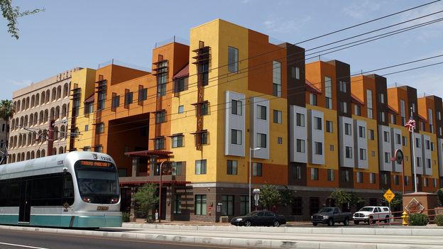 A Metro Light Rail train rolls by the Devine Legacy apartment building along Central Avenue in Phoenix. The energy-efficient complex includes 65