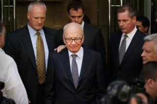 News Corp. Chairman Rupert Murdoch (C) looks down as he leaves the One Aldwych Hotel surrounded by his personal security team on July 15, 2011 in London, England.