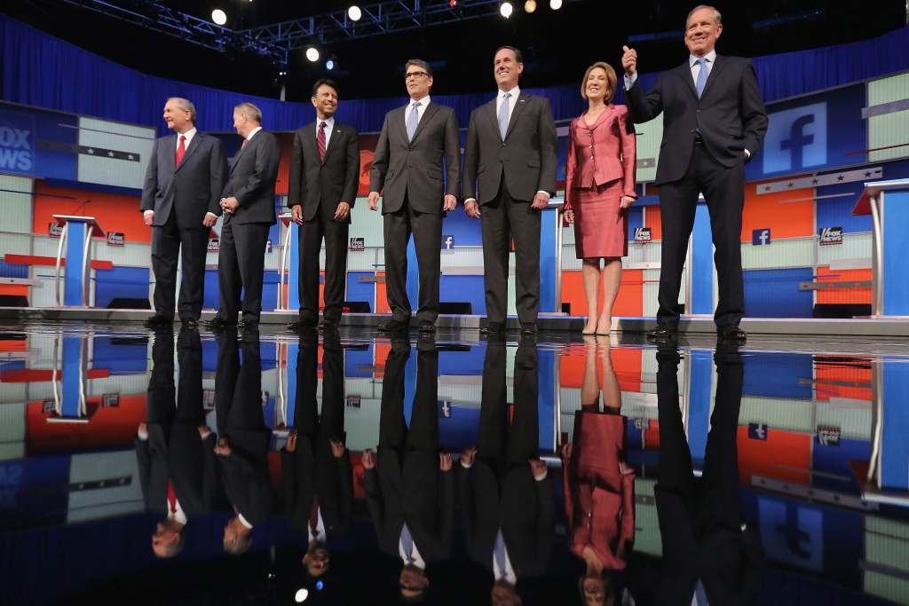Republican presidential candidates (L-R) Jim Gilmore, Sen. Lindsey Graham (R-SC), Louisiana Gov. Bobby Jindal, Rick Perry, Rick Santorum, Carly Fiorina and George Pataki pose for a photograph at the beginning of a presidential forum hosted by FOX News and Facebook at the Quicken Loans Arena August 6, 2015 in Cleveland, Ohio.