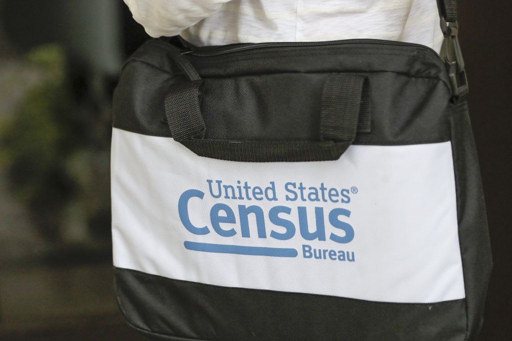 A U.S. Census Bureau worker carries a briefcase while knocking on the door of a home in August in Winter Park, Fla.