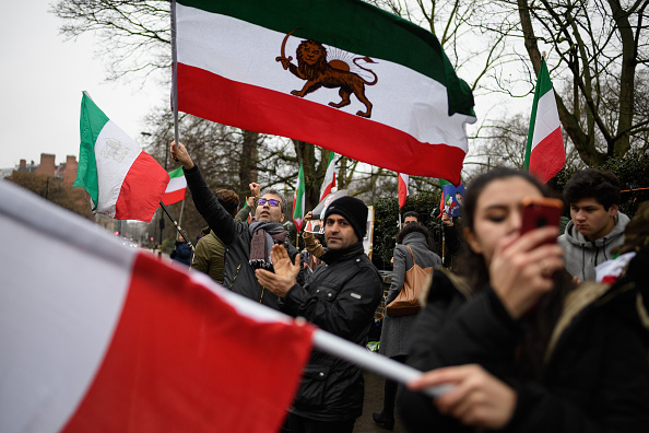 Anti-regime protestors wave flags as they demonstrate outside the Iranian embassy on January 2, 2018 in London, England.  Protests in Iran have seen at least 12 people die during violent clashes over recent days.