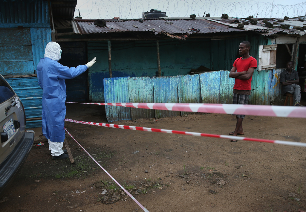 A doctor keeps a pedestrian away from the JFK Ebola treatment center on October 13, 2014 in Monrovia, Liberia. On Monday, the World Health Organization said the death rate in the Ebola outbreak has risen to 70 percent from a previous estimate of around 50 percent.