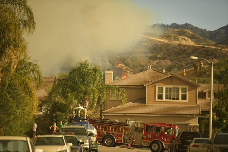 The Sand Fire smolders near homes off Golden Valley Rd Sunday afternoon.