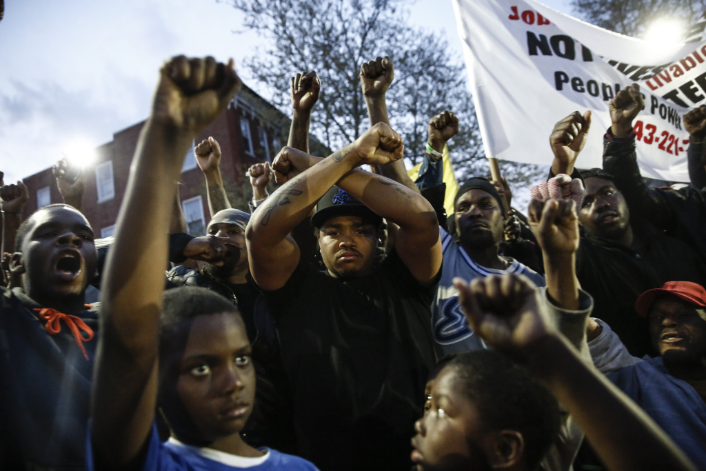 Protestors participate in a vigil for Freddie Gray down the street from the Baltimore Police Department's Western District police station, April 21, 2015 in Baltimore, Maryland.  Gray, 25, died from spinal injuries on April 19, one week after being taken into police custody.