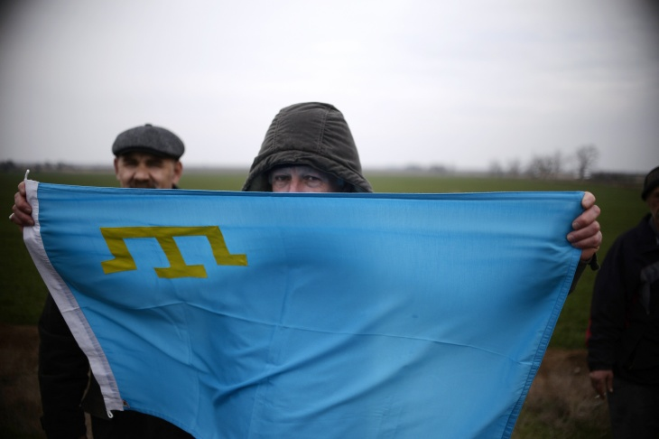A Crimean Tatar holds a Tatar flag during a pro-Ukrainian demonstration near the village of Ilinka on March 14, 2014, two days before a referendum in Crimea over its bid to break away from Ukraine and join Russia. The pro-Moscow leader of Ukraine's flashpoint Crimea peninsula called today on Russian-speaking eastern regions of Ukraine to hold their own referendums on switching over to Kremlin rule.