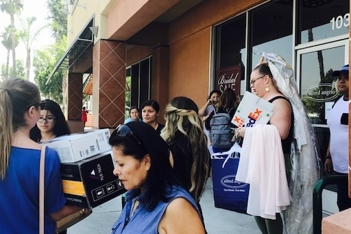 Alfred Angelo employees leave the company's West Covina store on July 14 fter the firm's abrupt closure and bankruptcy, as crowds ask for help finding their bridal gowns.