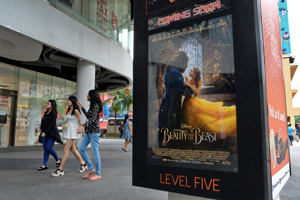 People walk past a poster for the film