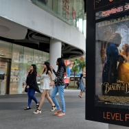 "People walk past a poster for the film ""Beauty and the Beast"" in Singapore on March 14, 2017."