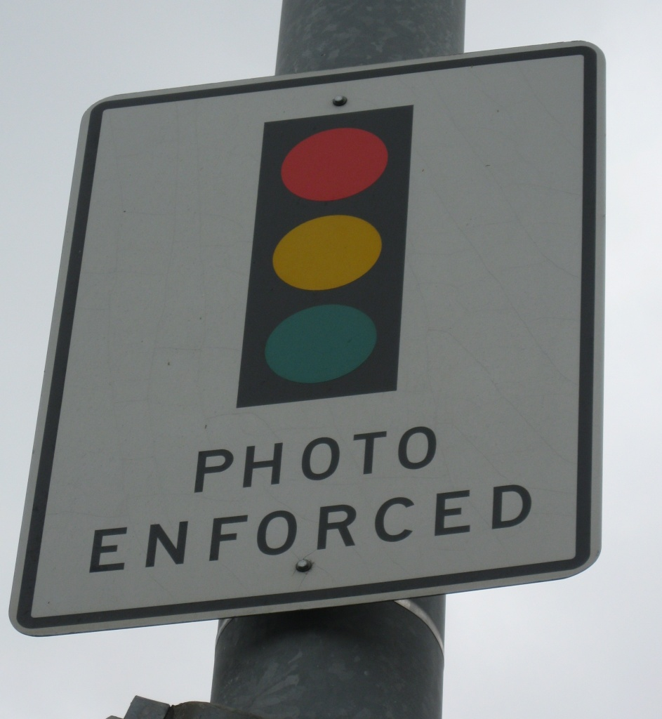 Signs such as this one in Laguna Beach warn drivers about red-light cameras in the city.