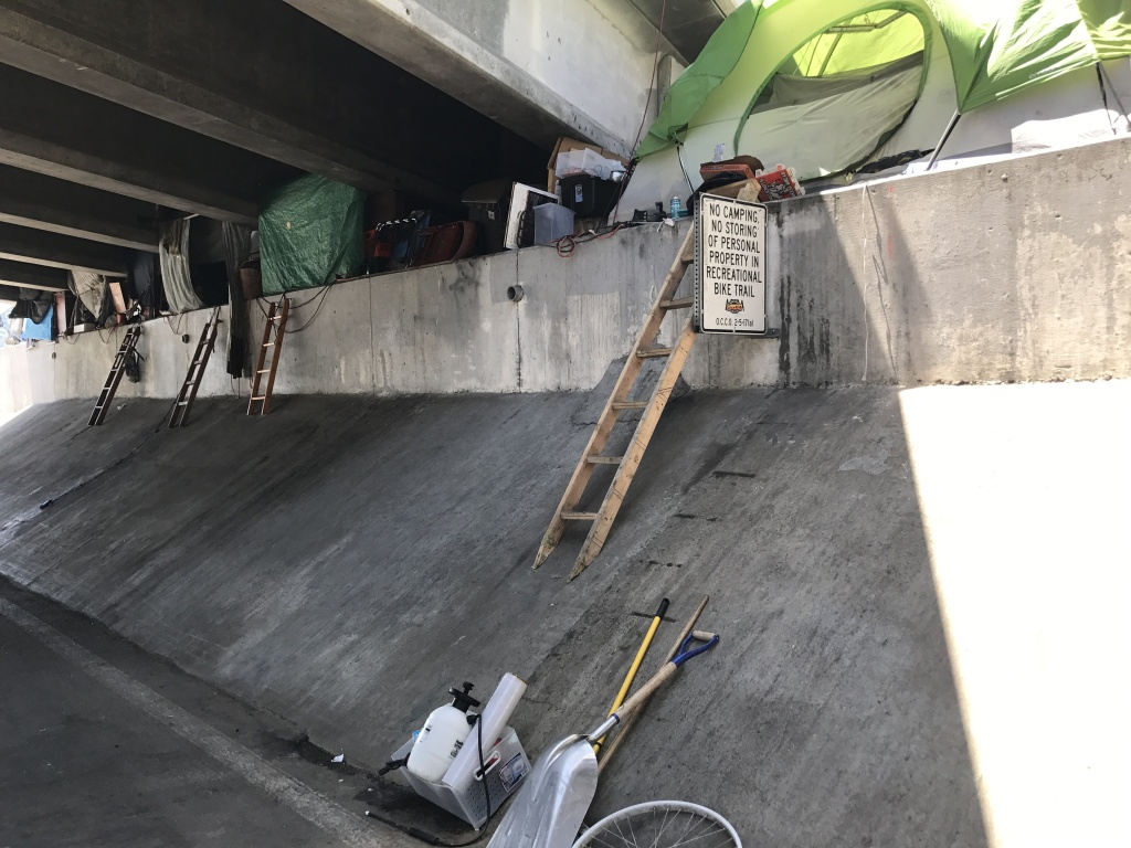 Tents line an underpass along the Santa Ana River near Angel Stadium.
