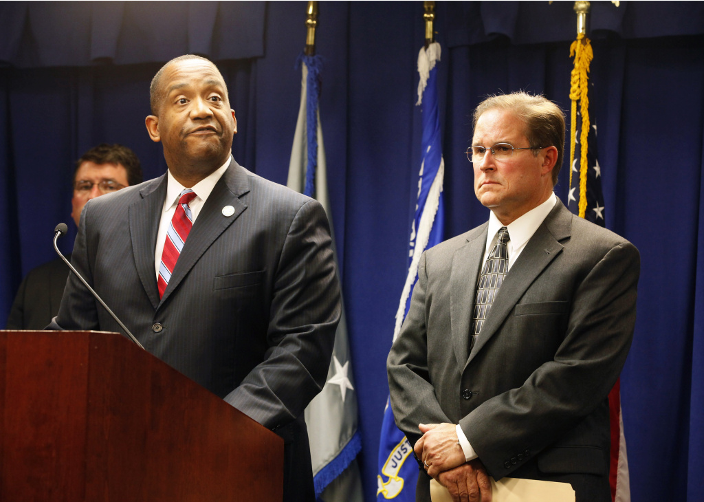 Andre Birotte, U.S. Attorney for the Central District of California, at podium, and Bill Lewis, Assistant Director in Charge of the FBI's Los Angeles Division, right, take questions on the five criminal cases filed against 18 current and former Los Angeles County sheriff's deputies as part of an FBI investigation into allegations of civil rights abuses and corruption in the nation's largest jail system, during a news conference in Los Angeles, Monday, Dec. 9, 2013. The FBI has been investigating allegations of excessive force and other misconduct at the county's jails since at least 2011. (AP Photo/Nick Ut)