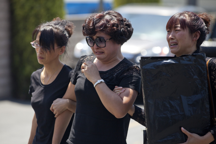 Songbo Ji, left, and his wife, Jinhui Du, far right, react after seeing their son, Xinran Ji, at the Universal Chung Wah funeral home in Alhambra, who was beaten by attackers near USC and later died in his apartment. His parents flew in from China with other family members to attend the funeral on Saturday.