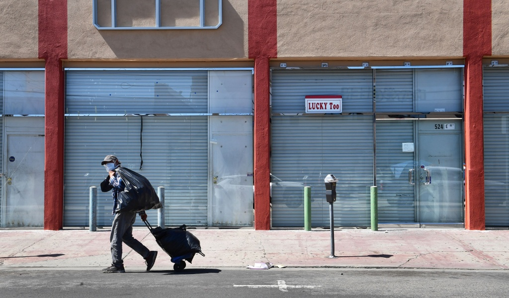 A man in a face mask walks past closed shopfronts in the Fashion District in Downtown Los Angeles, California on April 22, 2020, amid the novel coronavirus pandemic.