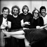 The Grateful Dead backstage in 1977. Left to Right: Bill Kreutzmann, Jerry Garcia, Bob Weir, Keith Godchaux, Mickey Hart, Phil Lesh, Donna Jean Godchaux. Photographer: Peter Simon