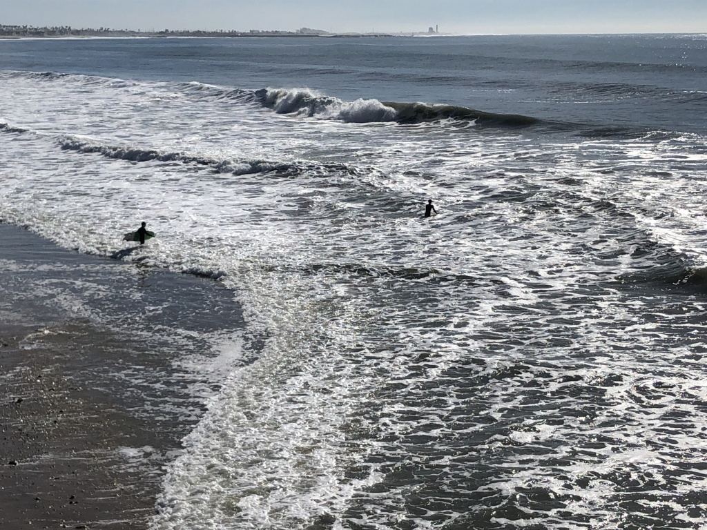 Two brave surfers venture into the high-surf advisory.