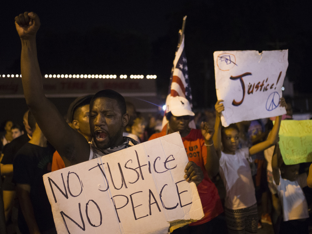 Demonstrators protest the killing of unarmed 18-year-old Michael Brown across the street from the Ferguson Police Department in Ferguson, Mo.