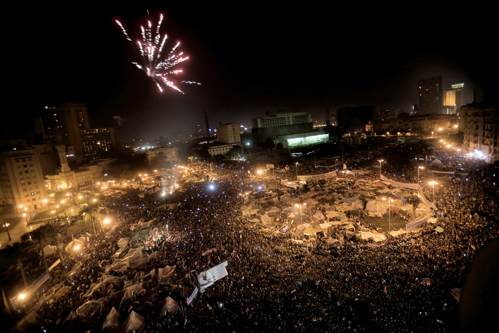 Egyptian anti-government protesters celebrate under fireworks at Cairo's Tahrir Square after president Hosni Mubarak stepped down on February 11, 2011.