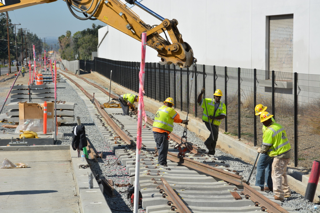 Workers line up rail on the tracks in Duarte for the Gold Line extension project on Friday, Feb. 21, 2014.